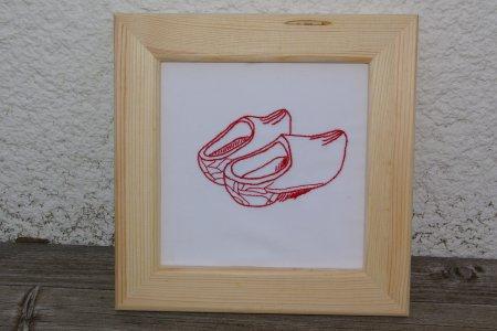Ein Paar Klompen in roter Linienstickerei